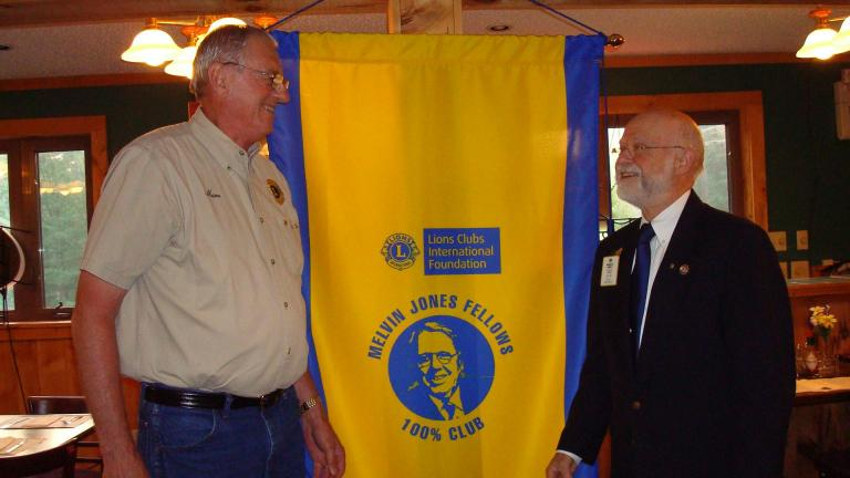 ADELE R. ARGOT/SPECIAL TO THE TIMES NEWS Effort Lions Club President Marvin Aylsworth proudly accepts the club's newest banner from PDG Bob Argot. The banner signifies that the club is a 100% Melvin Jones Club.