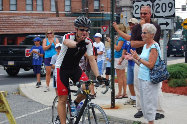 JOE PLASKO/TIMES NEWS WNEP Channel 16 meteorologist Joe Snedeker waves as he rides his bike into Depot Square Park in Tamaqua on Wednesday as part of his Go Joe XIII bike tour to raise funds for St. Joseph Center, Dunmore.