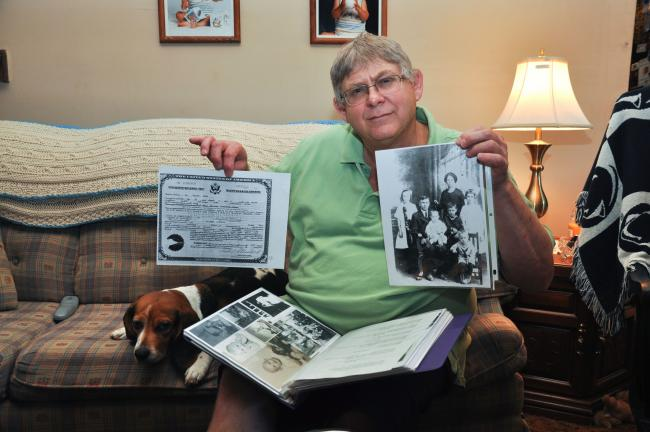 AMY ZUBEK/TIMES NEWS Joe Kalista displays a family photo of Casimir and Mary (Novak) Kalista; as well as a copy of his grandfather's naturalization papers from when he became a naturalized citizen on June 14, 1926. These were two of the many items…