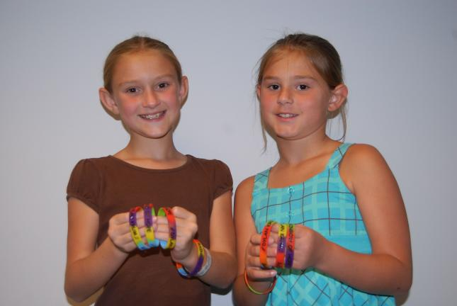 Ron Gower/TIMES NEWS Erin McGinley, 10, left, and her sister, Ally, 9, spent a portion of their summertime raising funds for another child in need. They are holding bracelets that they sold to raise funds for Dylan Krum, who passed away on July 15.