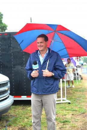Ron Gower/TIMES NEWS Carl Kern of Blue Ridge Communications TV-13 holds an umbrella while giving a weather report live from the Carbon County Fair near Palmerton. No umbrellas will likely be needed for the weekend events of the fair. The 11th annual…