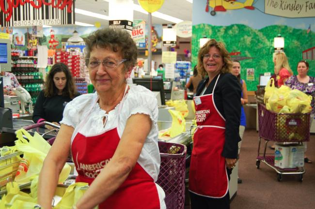 LINDA KOEHLER/TIMES NEWS Claudette Segear, Monroe County treasurer, front, and Debra Borger, CPA for Riley and Company, Inc., right, were Celebrity Baggers at Kinsley's ShopRite. They donated one hour of their time to help in the annual Grocer's…