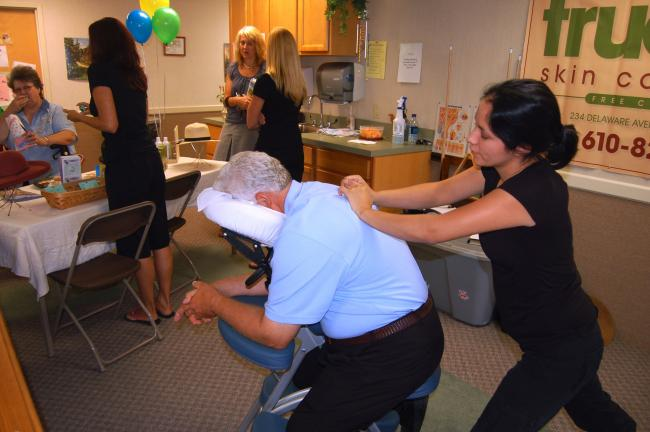 TERRY AHNER/TIMES NEWS Frank Deroza (seated) of Nazareth receives a massage from massage therapist Dana Montoya (standing) of True Spa and Skin Care Center of Palmerton during the Health Fair Wednesday at the Village at Palmerton.