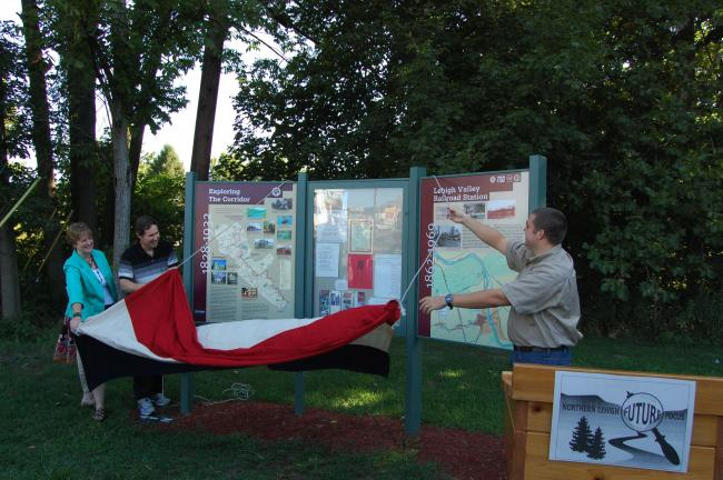 ELSA KERSCHNER/TIMES NEWS Virginia Savage, Dan Stevens and Silas Chamberlin unveil the three panel kiosk at the trailhead in Slatington.