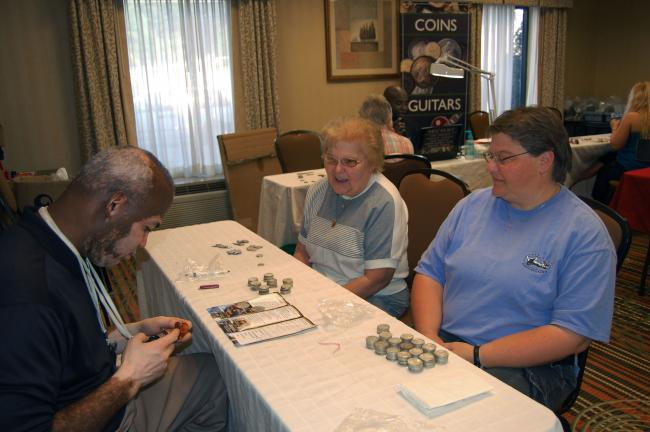 Regina Marhefka of Catasauqua, left; and her daughter, Karen Marhefka of Jim Thorpe, made a windfall selling old coins at the Ohio Valley Refinery Roadshow held last week at the Hampton Inn, Lehighton. They were assisted by Kenn Dees, manager.