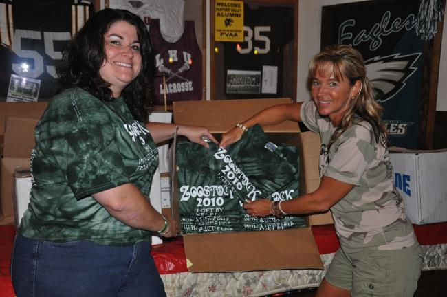 Ron Gower/TIMES NEWS Ann Marie Callabrese, left, and Lisa Hiles unpack special tee shirts for the 12th annual ZooStock, which will be held noon to 8 p.m. Monday at the Sports Zoo in Lansford. Proceeds benefit the Carbon/Tamaqua Unit of the American…