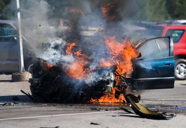 Bob Ford/TIMES NEWS Fragments fly during an explosion of a burning car following a head-on collision yesterday morning on SR443 in Mahoning Township. The four occupants inside the car were pulled to safety by passers-by moments before the car was…