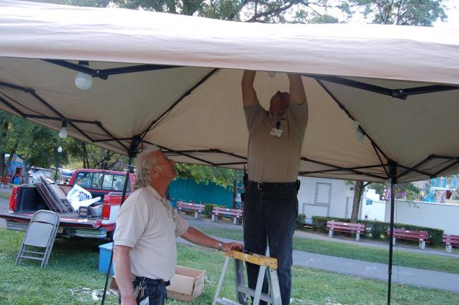TERRY AHNER/TIMES NEWS Mechanics Mike Dankanich (front) and Guy Anewalt (top), set up a first aid tent for Blue Mountain Health Systems this morning in preparation for the 21st Annual Palmerton Community Festival, which kicks off tonight in the…