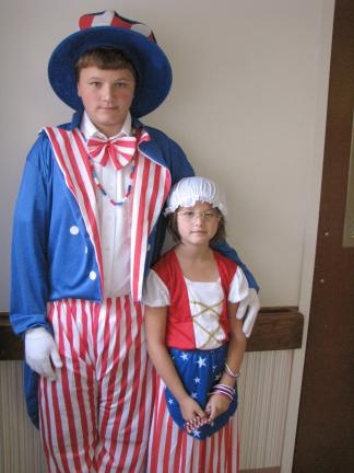 LIZ PINKEY/SPECIAL TO THE TIMES NEWS Tyler Calkins and Nyssa Sipley posed as Uncle Sam and Betsy Ross to distribute patriotic favors to the crowd during the annual 9/11 Remembrance Service, sponsored by the South Ward Playground Association.