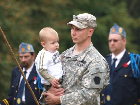 ANDREW LEIBENGUTH/SPECIAL TO THE TIMES NEWS Pennsylvania National Guard Sgt Edward Mady, an Iraq veteran, holds his one year old son, Troy, during the Schuylkill Flag Retirement Ceremony held recently at the Schuylkill Memorial Park in Schuylkill Haven.