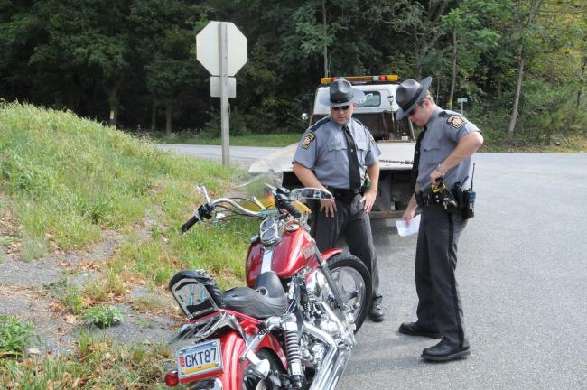 Larry Neff/Times News State police assess the damages on the front of one of two motorcycles involved in an accident Sunday in Lower Towamensing Township.