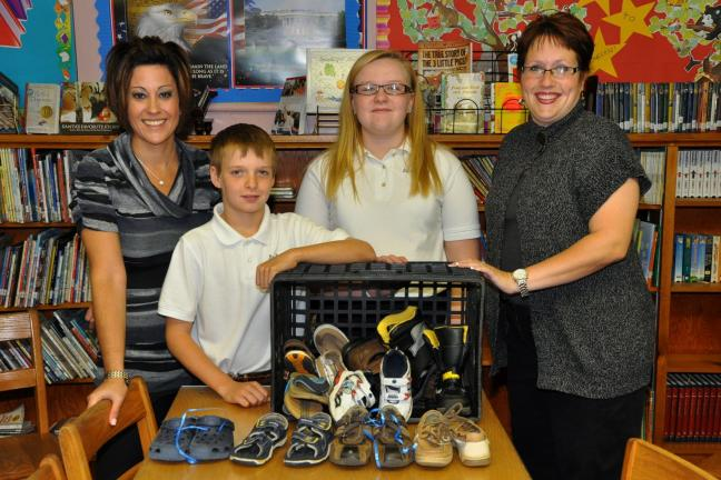 "VICTOR IZZO/SPECIAL TO THE TIMES NEWS Standing with just a few of the shoes being collected as part of Saint Joseph Regional Academy's participation in a program called ""Let them walk in our shoes"" are, left to right : Principal, Melissa Cuzzola;…"