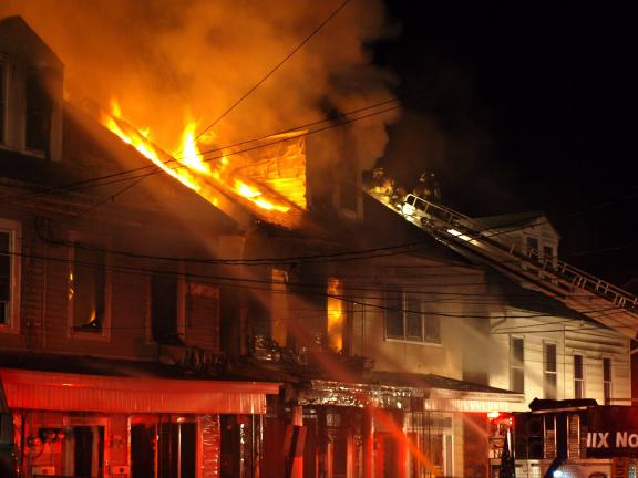 ANDREW LEIBENGUTH/SPECIAL TO THE TIMES NEWS Flames leap from a Shenandoah row home, one of 10 dwellings damaged in an early Saturday blaze.