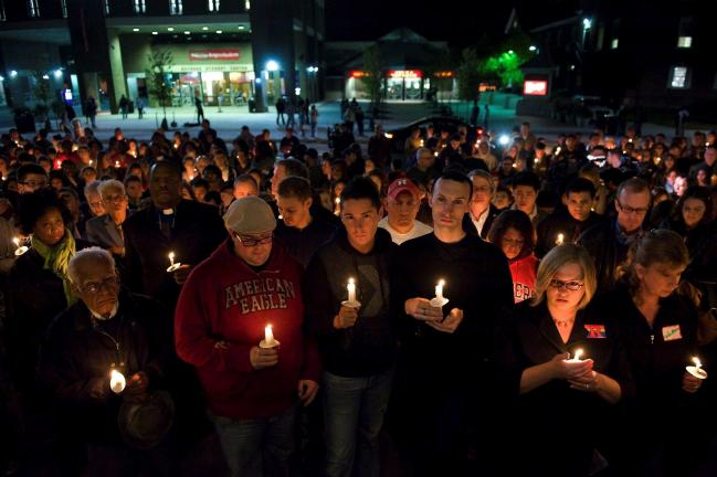 FILE- This Oct. 3, 2010 file photo shows people participating in a candlelight vigil for Rutgers University freshman Tyler Clementi at Brower Commons on the Rutgers campus in New Brunswick, N.J. Clementi jumped to his death off the George Washington…