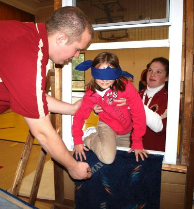 Andrew Leibenguth/Times News Tamaqua South Ward volunteer firefighters George Haldeman, left, and Sara Haldeman help guide second grader Kendra Kunkel, who is blindfolded to represent an escape from a smoke-filled room.