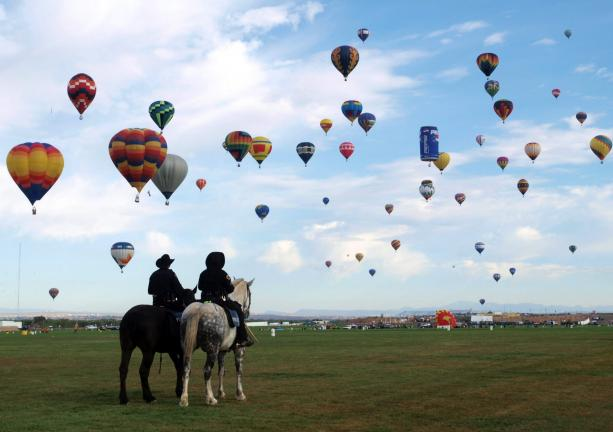 Albuquerque mounted police officers watch as 500 rainbow-colored and designer-shaped hot air balloons rise at Earth, Wind and Flyers-this year's theme at the Albuquerque International Balloon Fiesta.