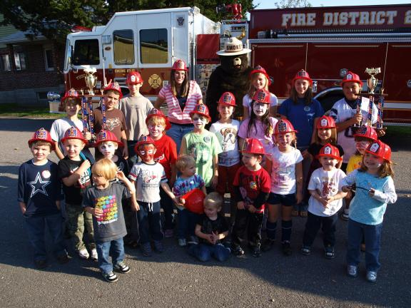 ANDREW LEIBENGUTH/SPECIAL TO THE TIMES NEWS Smokey the Bear shared in the festivities at the Tuscarora Fire Company's annual Safety Open House. Some of the young guests also display trophies won by the company at the state convention.