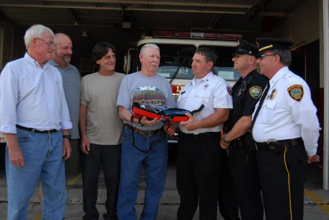 Ron Gower/TIMES NEWS Richard Bloom, center, vice president of Lehigh Fire Company No. 1, Lehighton, presents an external defibrillator to Patrick Mriss, captain of the Lehighton Fire Department. Lehigh Fire Company also gave defibrillators to police…