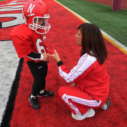 In this photo taken on Oct. 2, 2010, 9-year-old Jeremy Nativio holds his mother Stacy Nativio's finger as she offers some pre-game advice prior to a recent Neshannock, Pa. Pee Wee football game. Finding out their son had Down syndrome before he was…