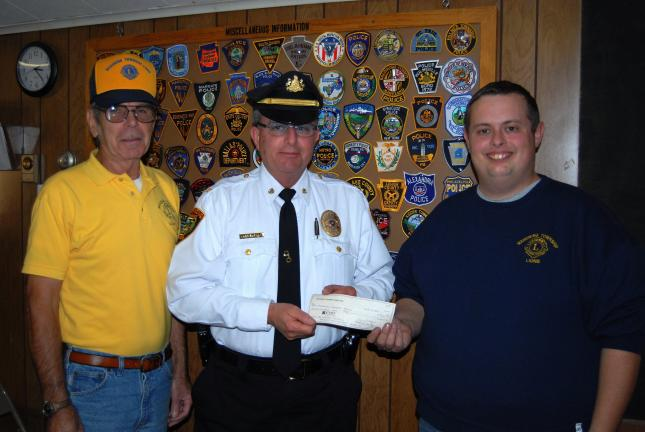 Ron Gower/TIMES NEWS Chief of Police Kenneth J. Barnes, center, of Mahoning Township, accepts check totaling $700 from Thomas Zimmerman IV, right, president of the Mahoning Township Lions Club. Looking on is Robert Hayman, a director with the club…