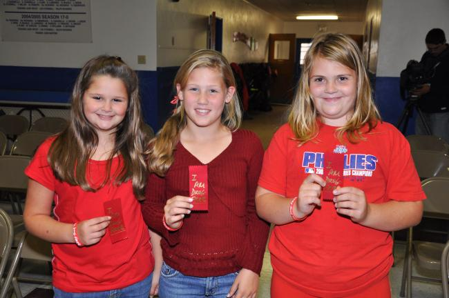 AMY MILLER Fourth grade students Kelsey Carroll, left; Caroline Snerr, center; and Rhiannon Malarkey, proudly show off their red ribbons saying they are drug free during a drug awareness program at St. Joseph's Regional Academy on Monday.