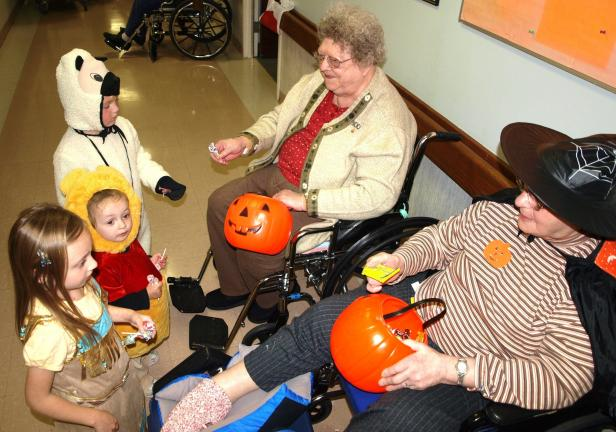ANDREW LEIBENGUTH/SPECIAL TO THE TIMES NEWS Residents lined the halls at the Hometown Nursing and Rehabilitation Center in Hometown to hand out candy to all the children. Pictured, from left, are Gracie Nallon, 6, dressed as Pocahontas, Isabel…
