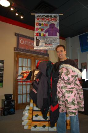 Gail Maholick/TIMES NEWS Mitch Schaffer, owner of Mobile Edge, 52 Blakeslee Blvd., Lehighton, is collecting gently used coats for needy children. Coats can be dropped off at the store until Dec. 31.