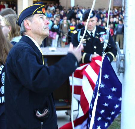 Quakake American Legion member and teacher Dale Kline raises the American Flag during the Tamaqua Area School District's Annual Veterans Day Observance.