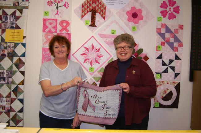 KAREN CIMMS/TIMES NEWS Valda Musselman, Palmerton, was the winner of the quilt block challenge in honor of Breast Cancer Awareness at The Quilted Crow in Lehighton. Presenting her with a tote bag and gift certificate is shop co-owner Jane Heckman.