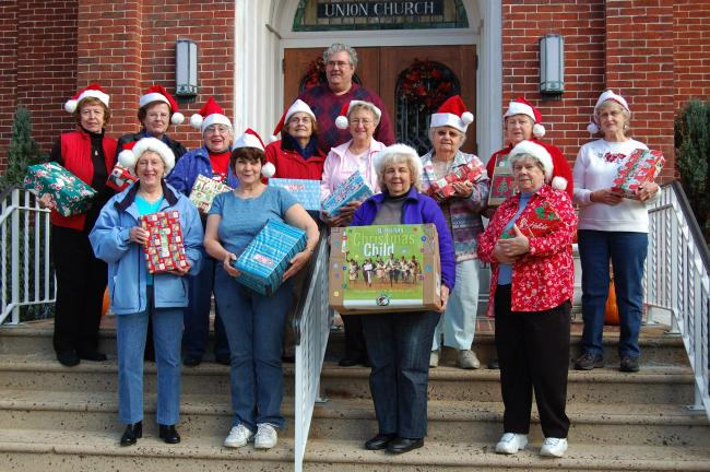 Shirley Eckhart, Donna Henninger, Lavonne Rehrig, Edith Spadt, Phyllis Geiss, Geraldine Christman, Carol Bloss, Pauline Santee, Pat Ritz, Dorothy Biscar, Beverly Putt and Shirley Fritz, with the Rev. Martin Nuscher in the back, helped pack the…