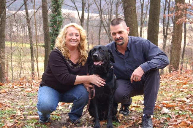 CHRIS PARKER/TIMES NEWS JoAnn and Neil Pilston of Walker Township with Diesel. The couple is caring for Diesel until his owner, a Vietnam vet who has been hospitalized for a year, can once again take care of him.