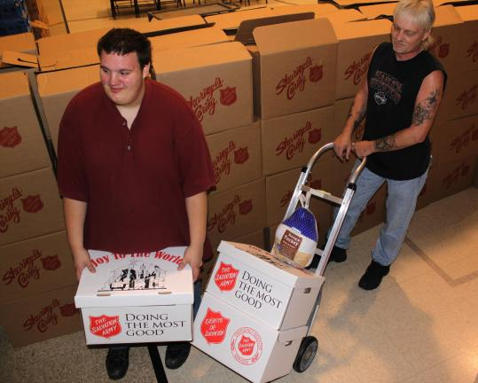 Tamaqua Salvation Army volunteers Frank Latham, left, and Norm Coxe help carry turkeys and food boxes to people's vehicles during the Salvation Army's annual Thanksgiving food distribution.