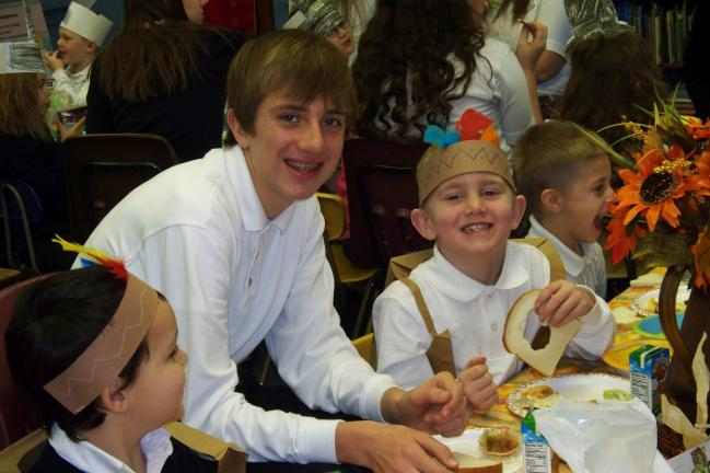 Ethan Vermillion and Matthew Rehrig share at the harvest table during the first Thanksgiving reenactment at Our Lady of the Angels Academy.