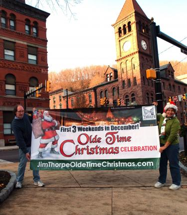 AL ZAGOFSKY/SPECIAL TO THE TIMES NEWS Bill Eckert, chairman of the Jim Thorpe Olde Time Christmas, and Parade coordinator Karen Freese hold sign announcing the event which will run on the three weekends of December 3-5, 11-12, and 18-19.