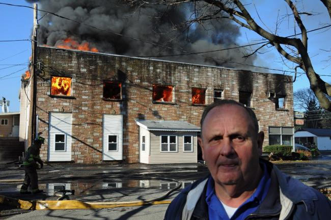 LARRY NEFF/SPECIAL TO THE TIMES NEWS Carl Cyphers, owner of Cyphers Truck Parts along West Main street in Stroudsburg watches as his business goes up in flames Monday morning.