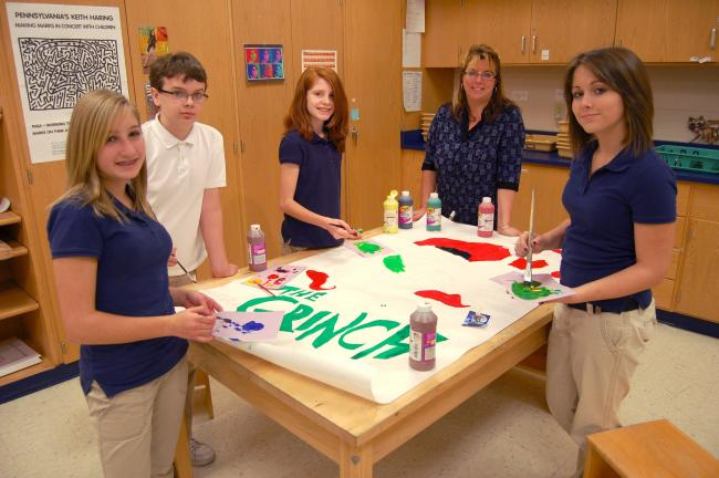 "JOE PLASKO/TIMES NEWS Tamaqua Area Middle School Specialty Art Group students (from left) Brooke DeHart, David Kunkel, Nicole Prantow and Olivia Morrison work on a poster for ""How the Grinch Stole Christmas"" under the watchful eyes of instructor Kim…"