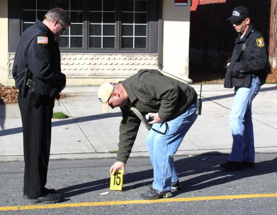 ANDREW LEIBENGUTH/SPECIAL TO THE TIMES NEWS Tamaqua Police Detective Henry Woods, center, investigates the robbery scene at We R Cigarettes with fellow officers.