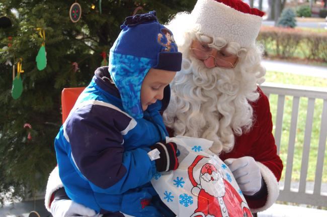 TERRY AHNER/TIMES NEWS Isaiha Leickel, 4, of Slatington, anxiously looks through his goody bag as he sits on the lap of Santa Claus Saturday in the Palmerton Borough Park bandstand.