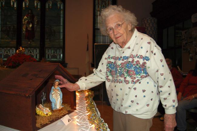 TIMES NEWS FILE PHOTO Mildred Zeiser places the figures in her nativity at a previous Creche/Nativity Display at St. John's Lutheran Church, Jim Thorpe. A variety of settings for the Holy Family will be displayed this weekend.