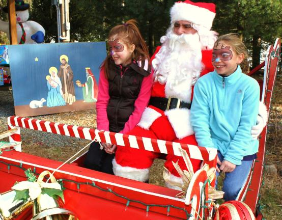 ANDREW LEIBENGUTH/SPECIAL TO THE TIMES NEWS Pictured sitting with Santa on his sleigh during the annual Owl Creek Reservoir Commission's Christmas with Santa are Jennifer Frederickson, 9, left, and Peyton Gilbert, 10 who had reindeer painted on…