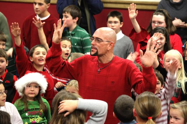 ANDREW LEIBENGUTH/SPECIAL TO THE TIMES NEWS St Jerome's new music director Paul Mulhern rallies the students for their dance performance in the aisles during the St Jerome Regional School's first annual Performing Arts Christmas Concert held…