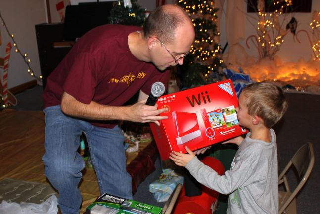 ANDREW LEIBENGUTH/SPECIAL TO THE TIMES NEWS Pastor Ed Noftz gives Aaron Bauder, 5, his 'First Gift', a Nintendo Wii game system, after his name was drawn during the fourth annual free 'First Gift' Community Christmas Program held at the New Life…
