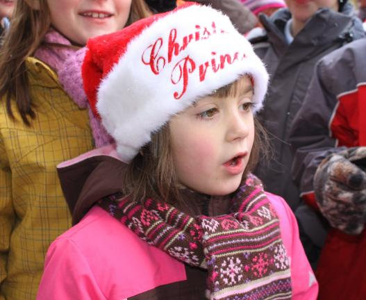 ANDREW LEIBENGUTH/SPECIAL TO THE TIMES NEWS Kadence Dietrich, 5, sings 'We Wish You A Merry Christmas' outside Klingaman's Office Equipment with 122 other St Jerome school-mates, teachers, and parents while caroling in downtown Tamaqua. Kadence is…