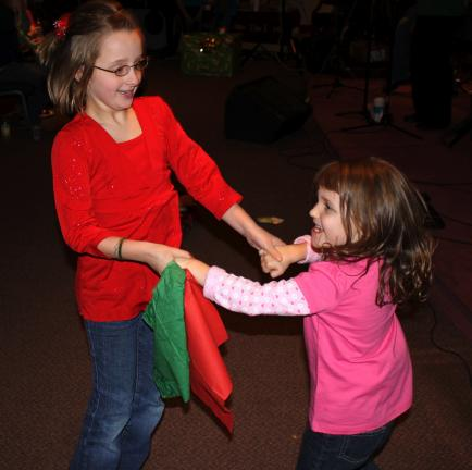 ANDREW LEIBENGUTH/SPECIAL TO THE TIMES NEWS Aurora Kranch, 9, and Pamela Miller, 5, both from Tamaqua, vent their holidays energy while dancing to the up-beat holiday music played at the Salvation Army Christmas Benefit Concert held recently.