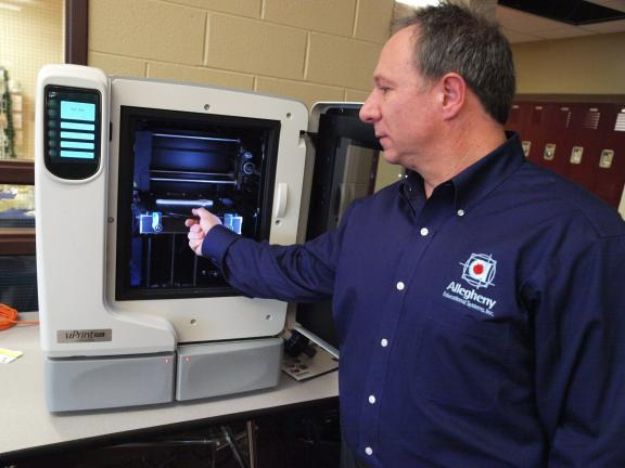 AL ZAGOFSKY/SPECIAL TO THE TIMES NEWS Gary Lavieri of Allegheny Educational Systems demonstrates the Dimension uPrint 3D printer, a machine that produces a three-dimensional plastic model from a 3D CAD file.
