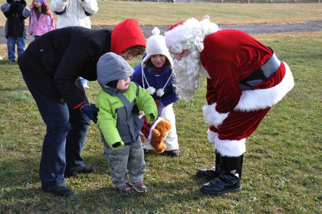 Ron Gower/Times News Santa greets children Donovan Hydro, age 2, left, and Emily Krajnak, 18 months, of Summit Hill, while looking on is Lilly Dunn of Summit Hill.