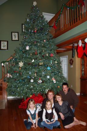 LINDA KOEHLER/TIMES NEWS Annamarie and Shawn Bauer of Kunkletown pose around their majestic 15' Christmas tree with their triplets, Sarah, Jill and Amy.