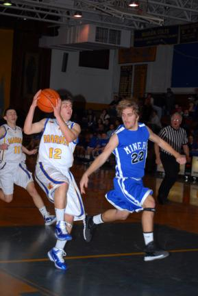 RON GOWER/TIMES NEWS Marian Catholic's Ryan Karnish (12) drives past Zach Dixon of Minersville. Karnish was the high scorer for the Colts with 10 points, including two three-point baskets.