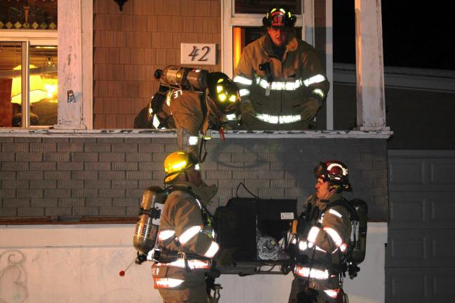Andy Leibenguth/special to the times news Firefighters remove a wood pellet stove, the source of last evening's house fire in Coaldale.