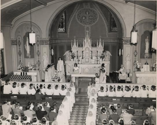 SPECIAL TO THE TIMES NEWS Lehighton's Sts. Peter and Paul Catholic School is celebrating its 125th anniversary this year. Seen here is the adjacent church, which is just one year older, during one of its early May Procession ceremonies.